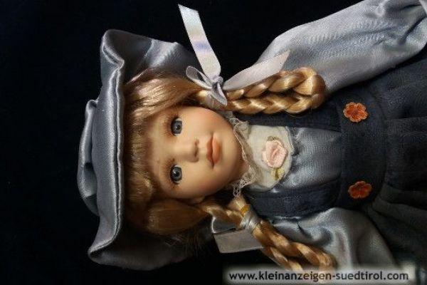 Porzellanpuppe mit blonden Zöpfen